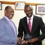 Makerere University vice chancellor Prof Barnabas Nawangwe giving Alex Esagala his award on 7th November 2018